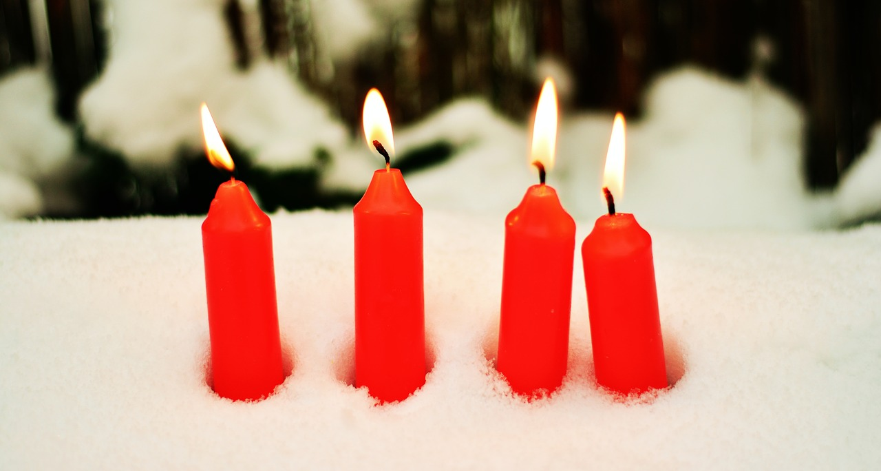 Four red candles burning in a snow bank